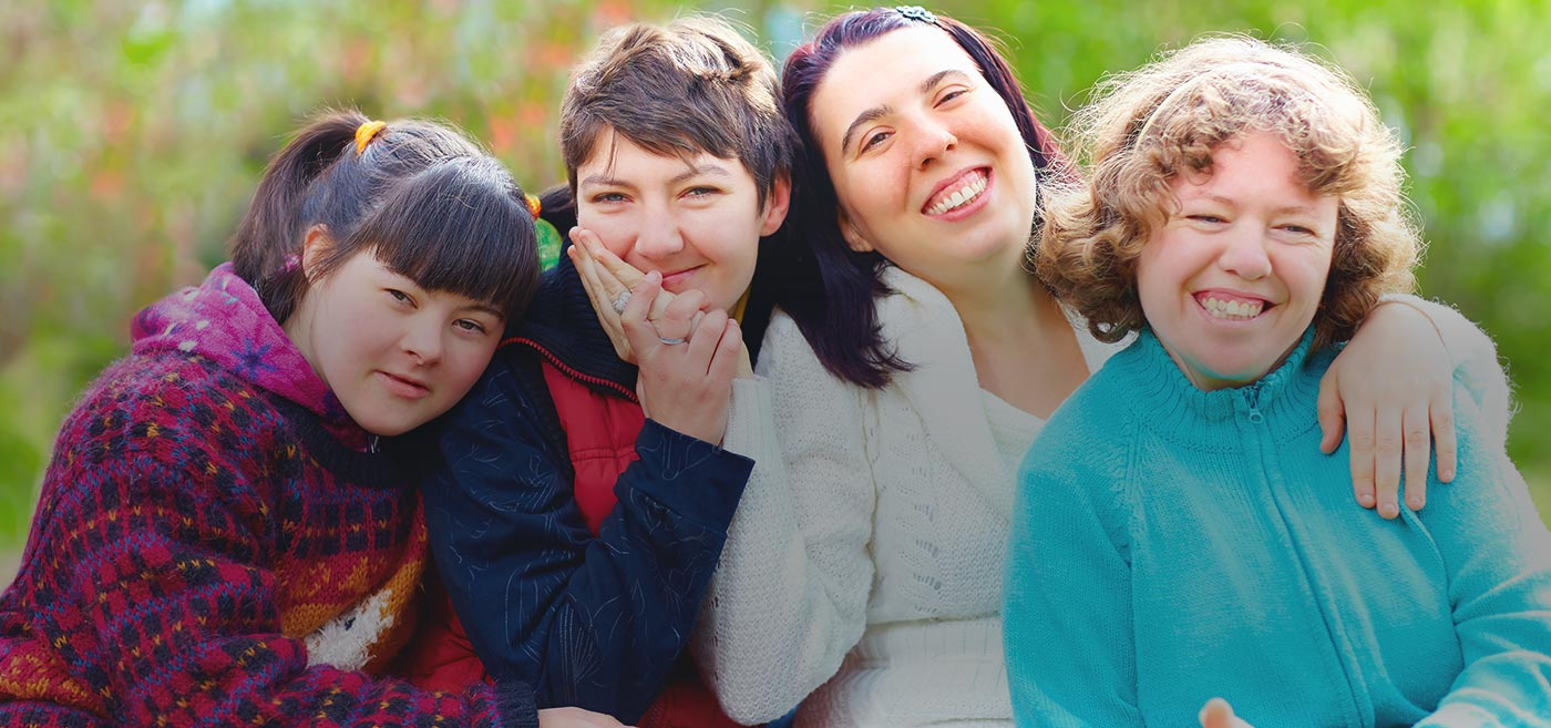 Group of Developmentally Disabled Woman smiling & embracing each other