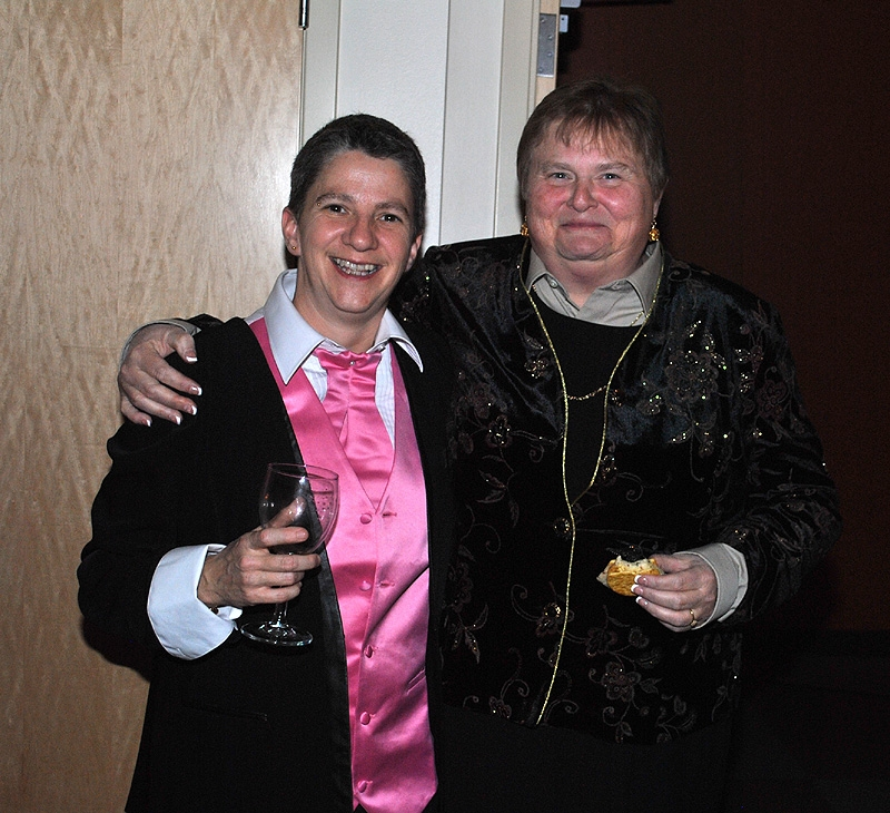 Two women toasting wine at indoor party
