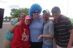girl with wacky blue wig posing with people