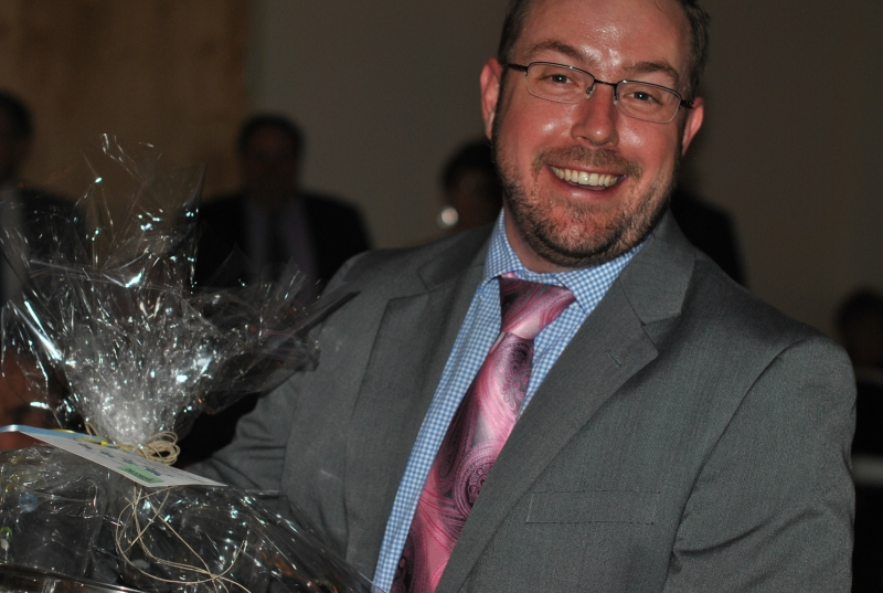 man smiling with raffle basket