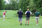 golfers watching man tee off
