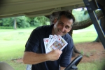 golfer holding up four king playing cards