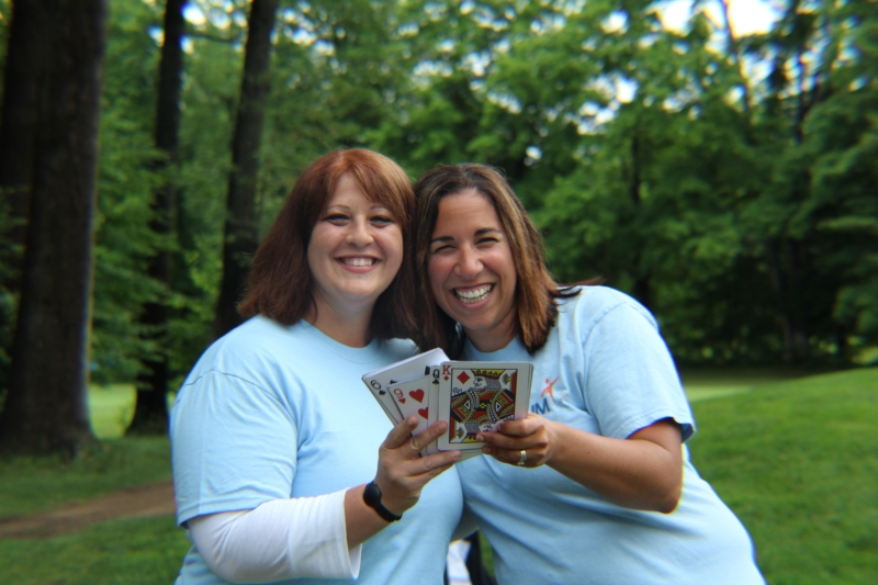 two aim volunteers smiling and holding playing cards