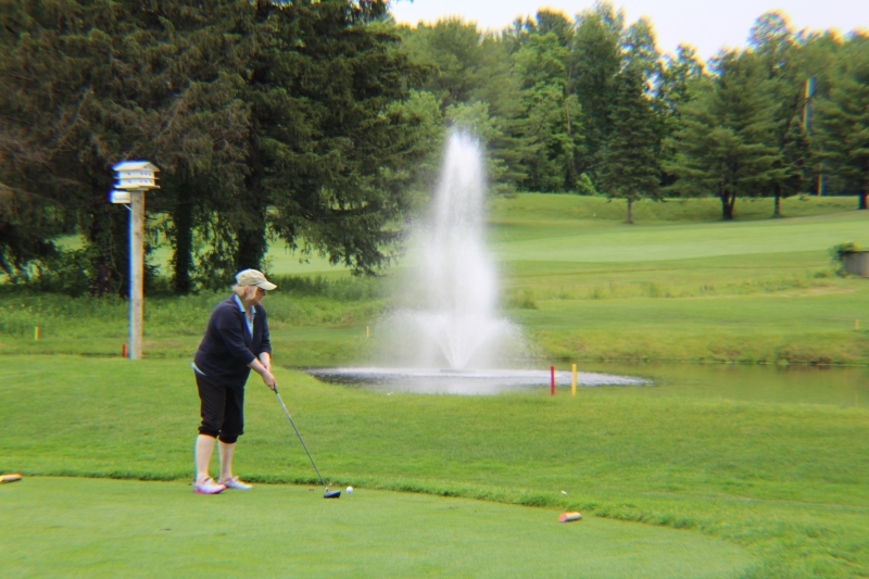 woman teeing off over a pond