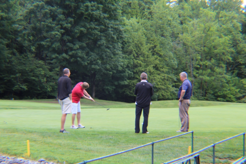 golfers watch a man hit the green