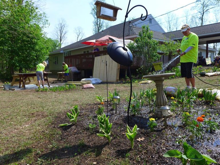 man waters flowers and fills up bird bath