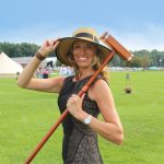 Woman standing in grassy field holding brim of sun hat and croquet mallet over her shoulder smiling