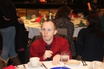 Man in red shirt seated at table