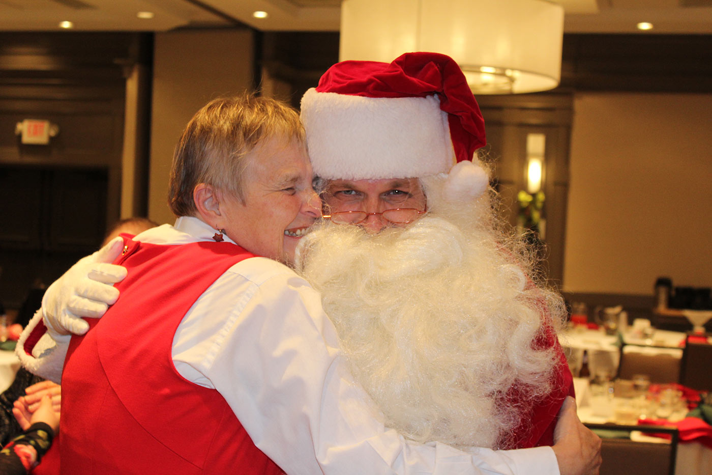 Santa hugs older women
