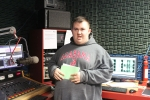 Man in grey sweatshirt in radio booth