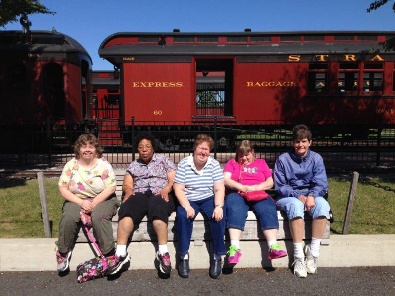 the five ladies sitting on bench with express train in background