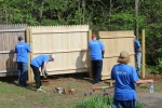 Men building a wooden fence and doing spring clean-up at the backyard