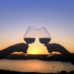Silhouette of two wine glasses cheersing over a sunset on a lake