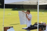 Tournament Judge writing fields on white board score board at AIM Services Croquet on the Green event