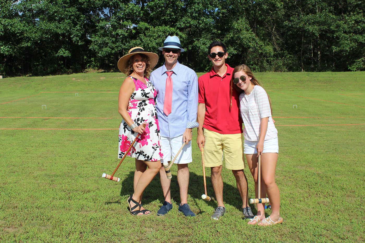 Group of people playing croquet and holding rackets
