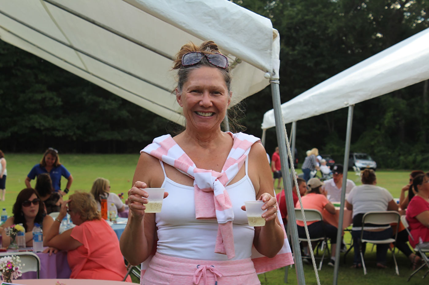 woman showing off two white wine cups