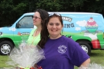 woman in purple tshirt smiles with raffle baskets