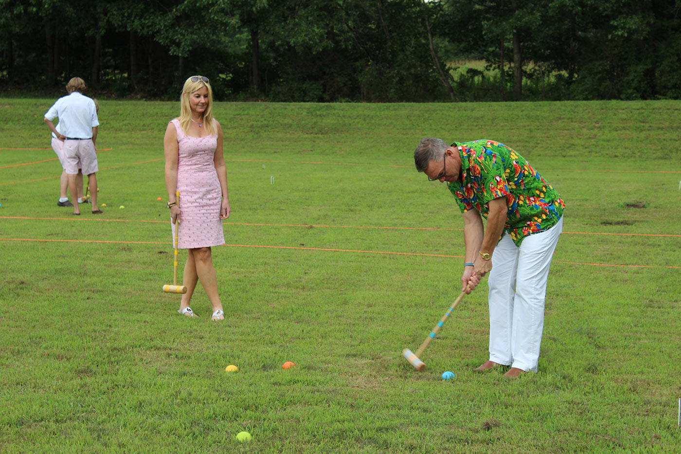 woman in pink dress watching partner hit ball
