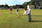 woman swings stick at black ball on field