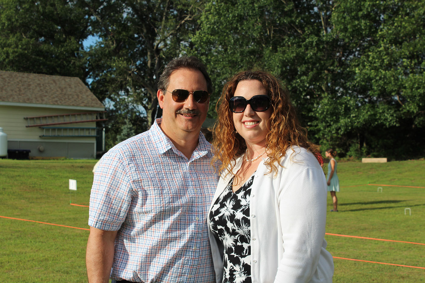 Couple dressed up pose for a picture at AIM Services Croquet on the Green event