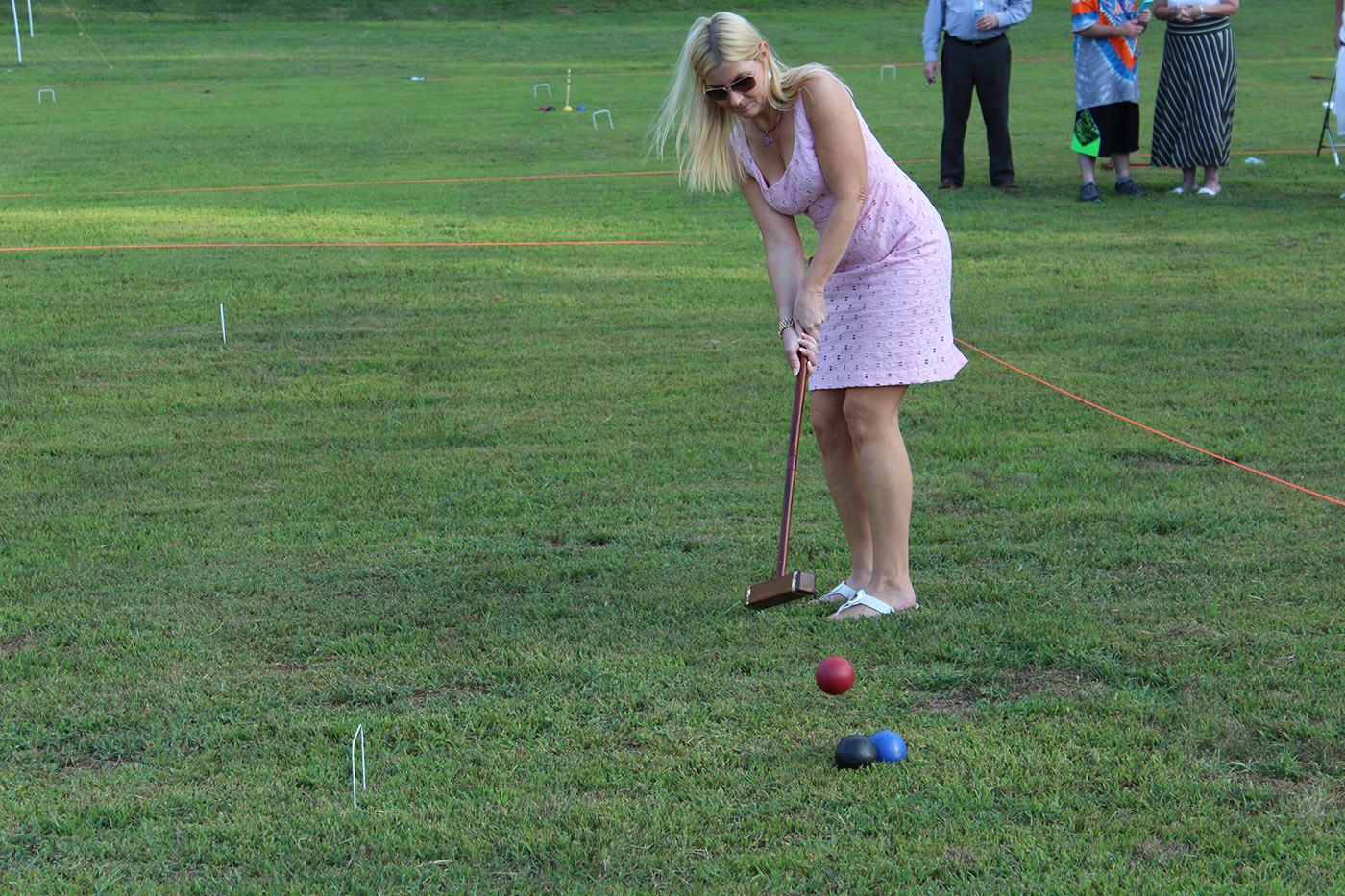 woman in pink dress hitting ball