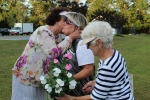 Old women kiss and hug one another in white clothes outdoor