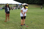 women wearing yellow visors playing croquet
