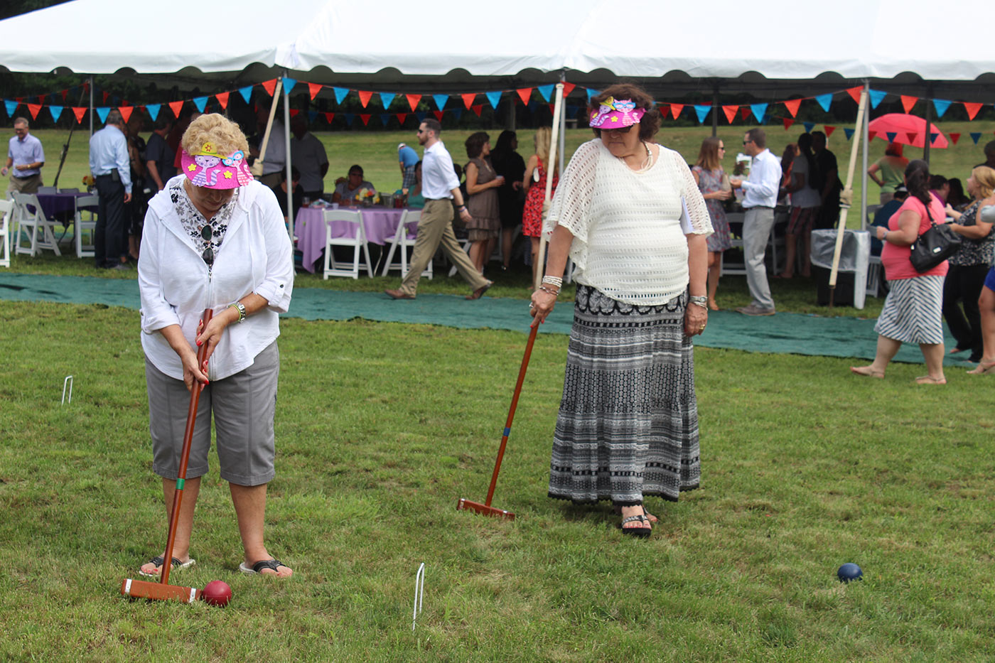 two women in goofy pink hats playing croquet