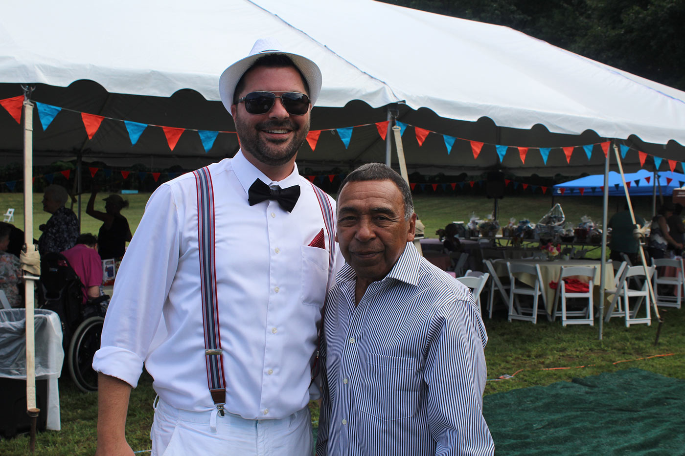 man in white hat smiles with guy in stripes