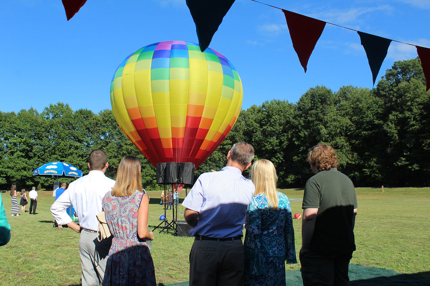 people watching multicolored hot air balloon take off