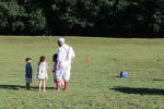 man talking with kids on field