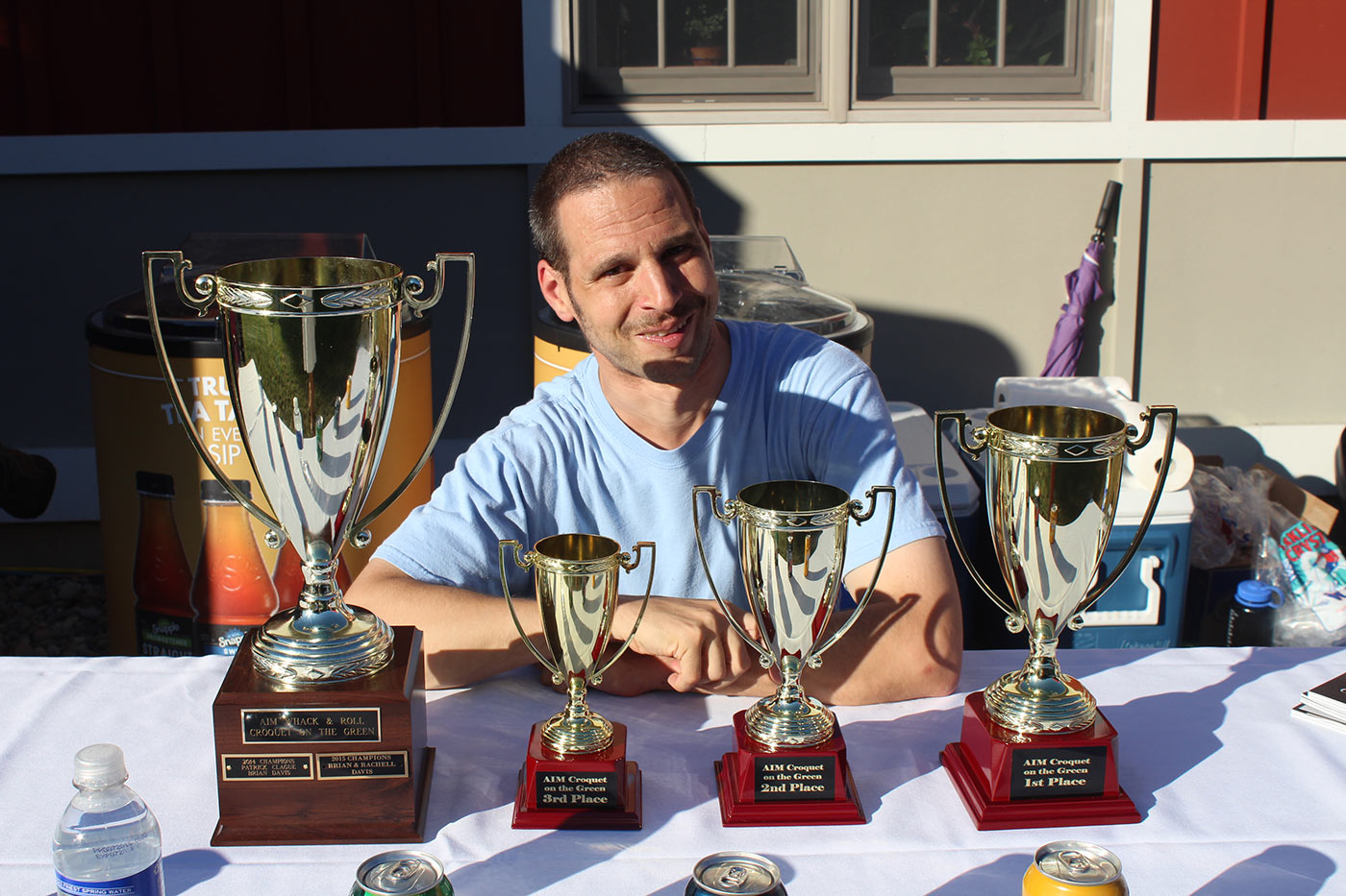 man posing with the four different trophies