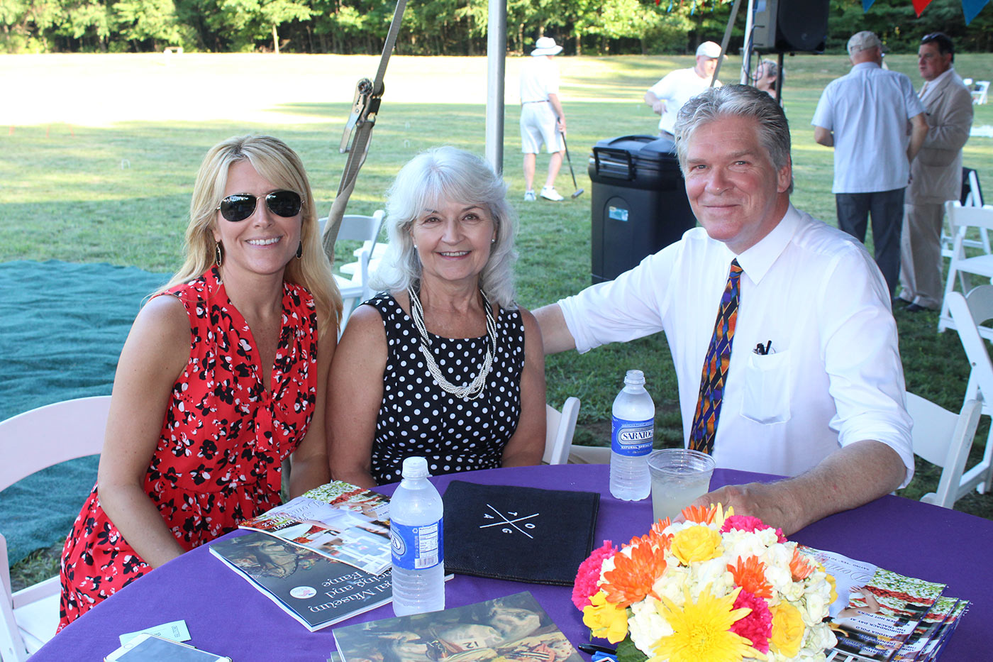 three people sitting at purple table