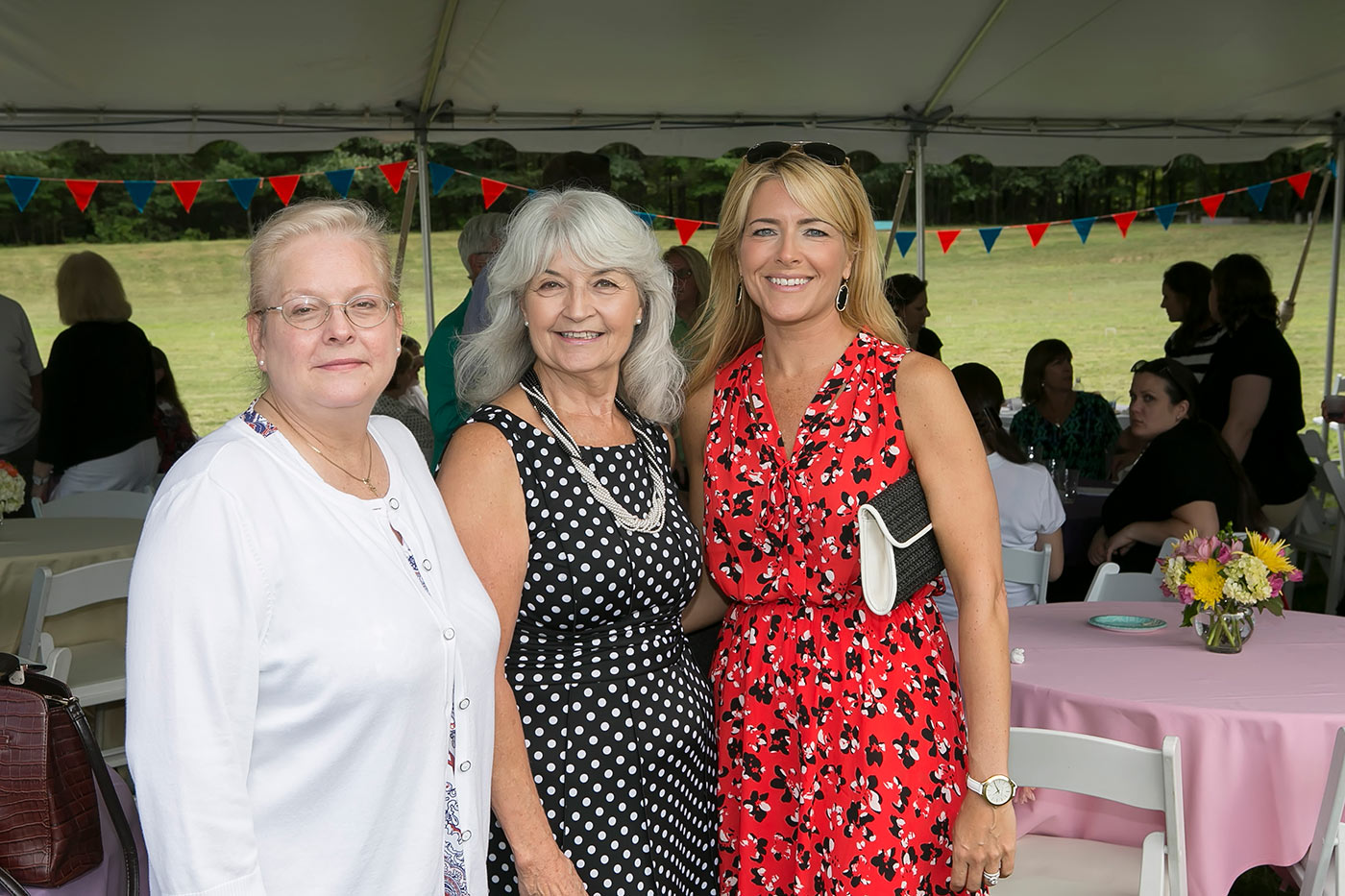 three women smiling under the tent