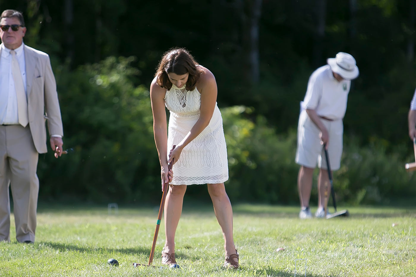 woman in white dress strikes ball