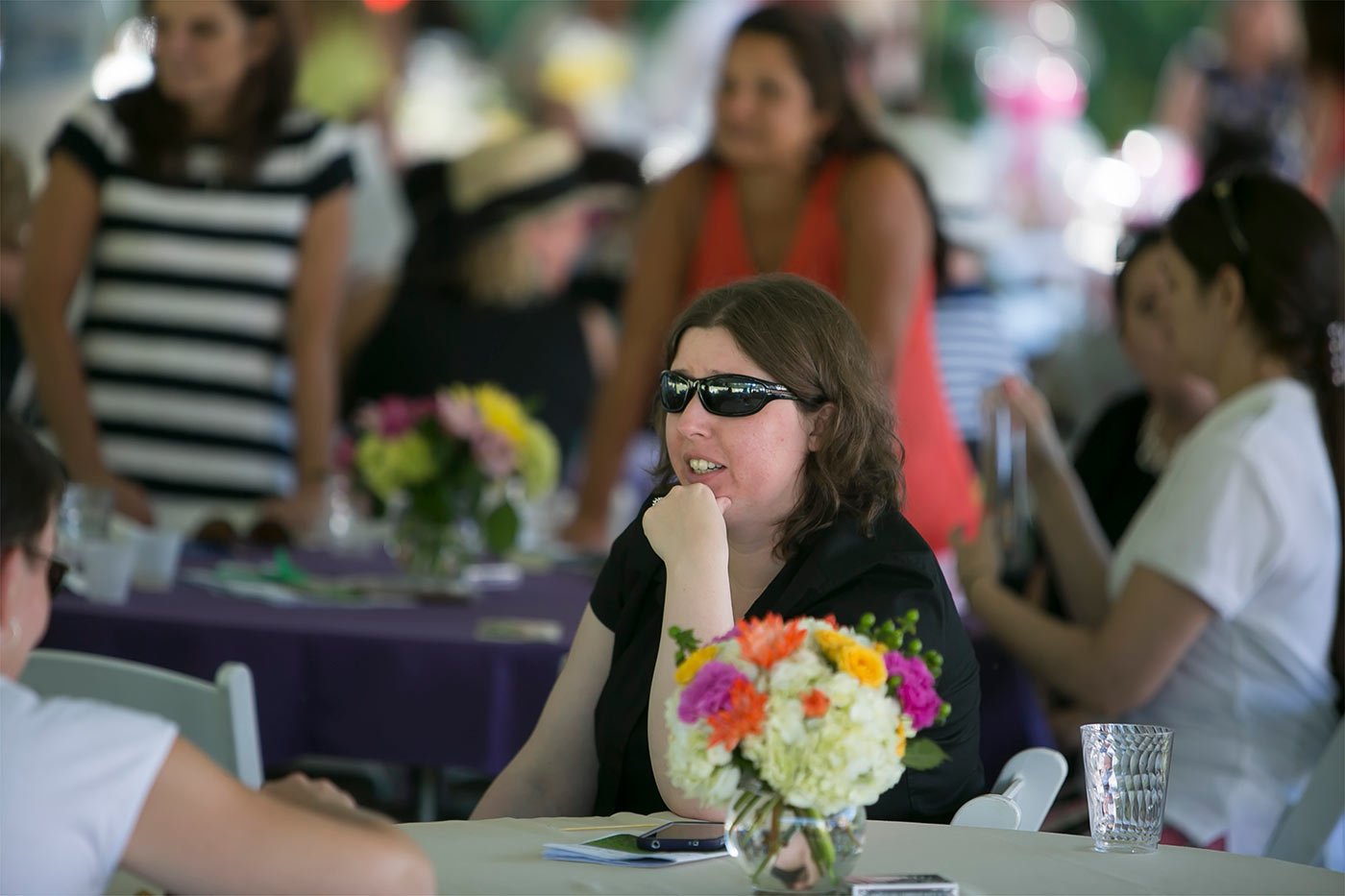 woman in black and sunglasses at table