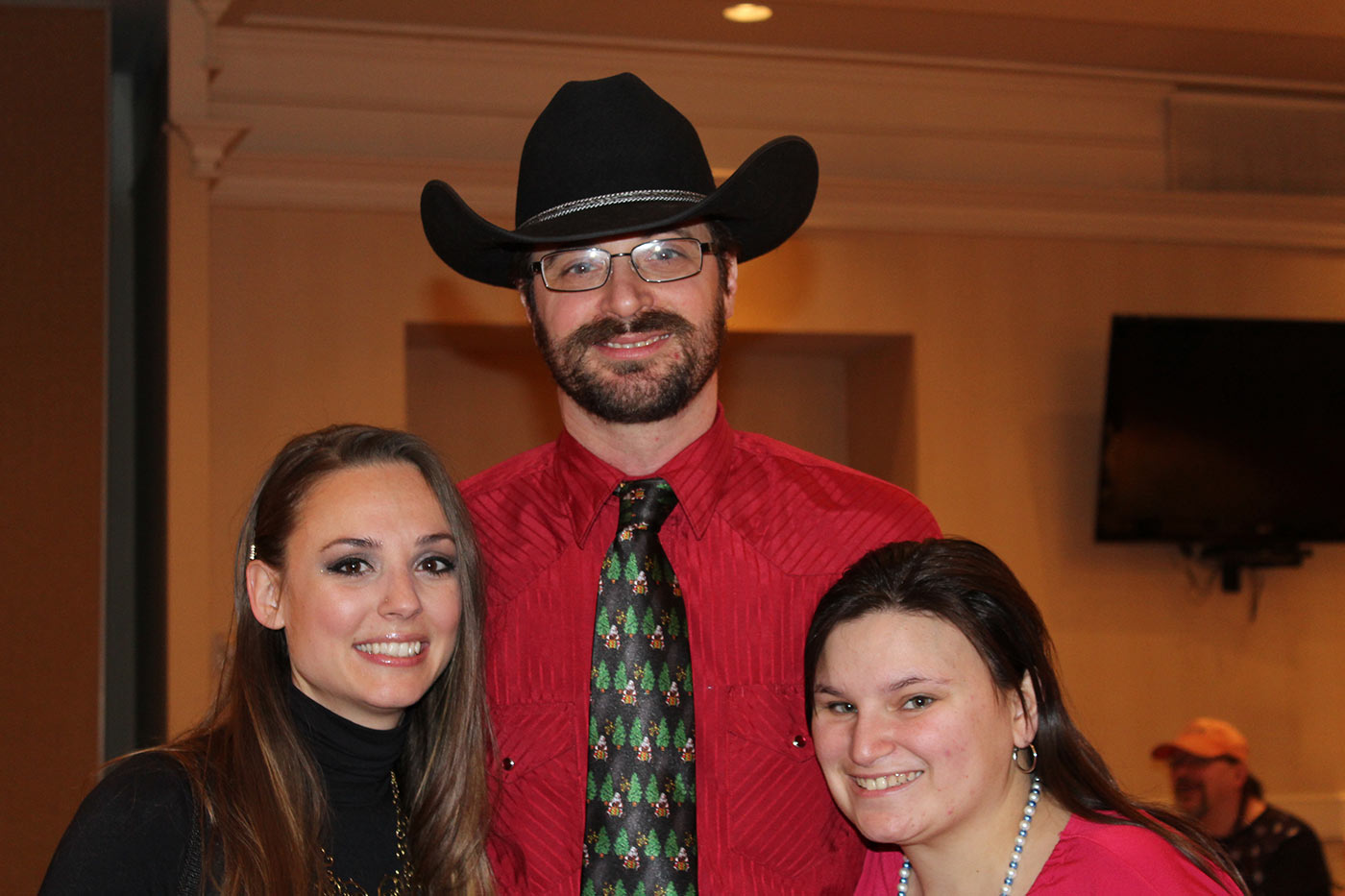 man in cowboy hat smiling with two women
