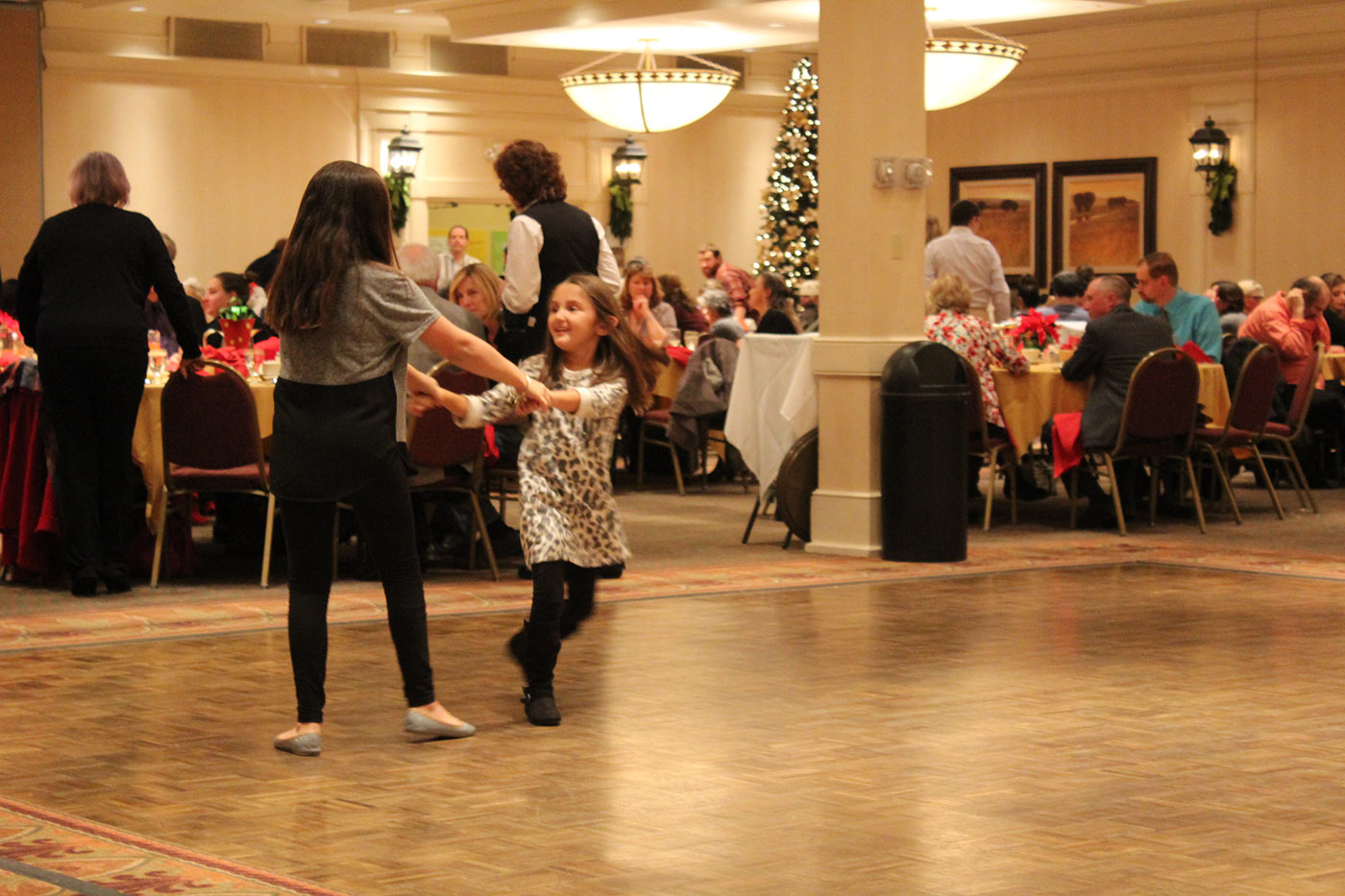 two little girls holding hands swinging around on the dance floor