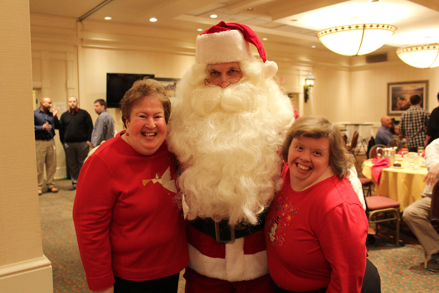 two women smiling with santa claus