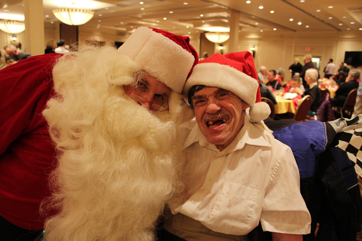 two men in santa suits smiling