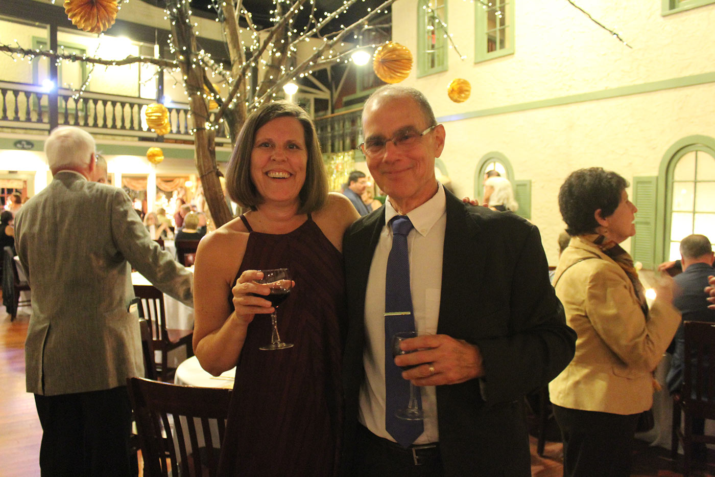 man and woman holding red wine glasses smiling for camera
