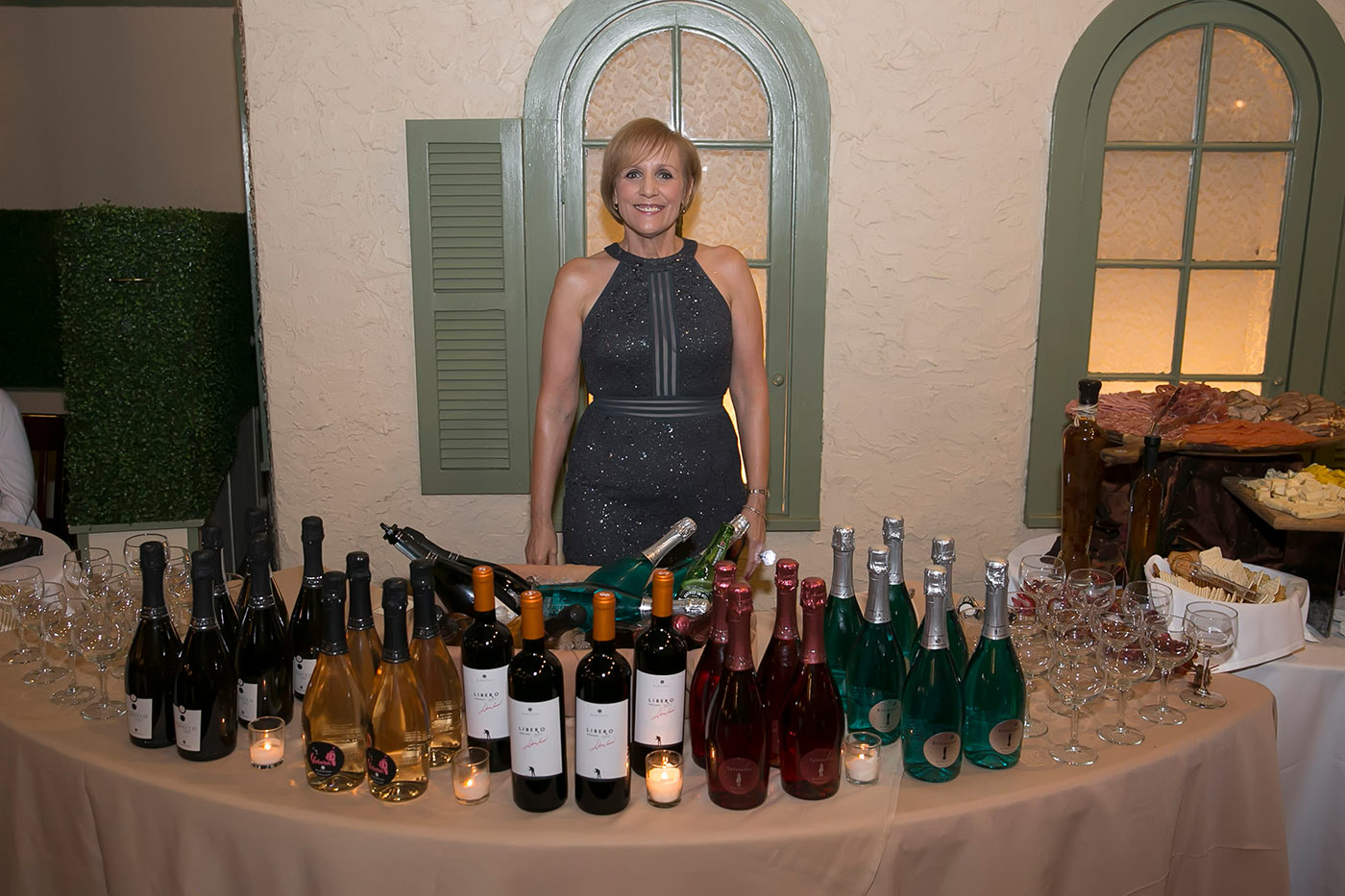 woman serving wine smiles for photo