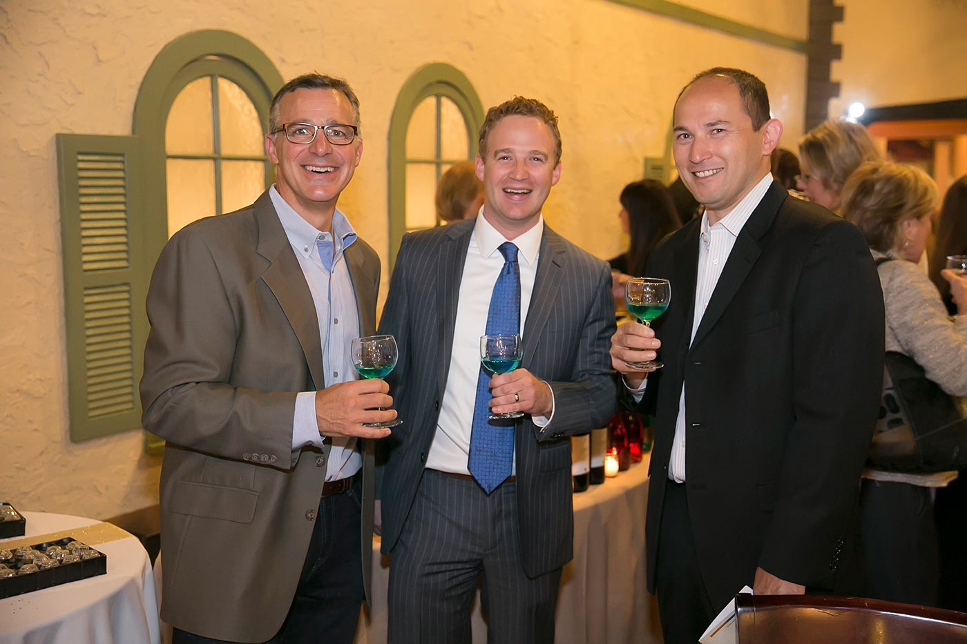 three men posing with green and blue drinks