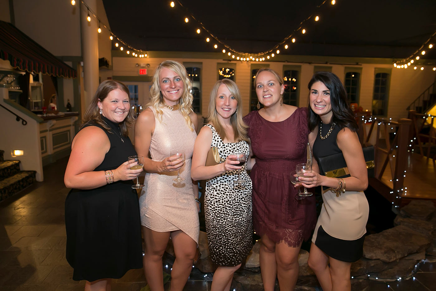 group of young women smiling with wine