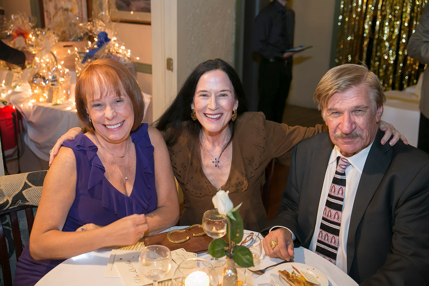 three guests smiling at a table