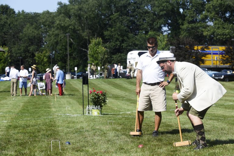man carefully lines up croquet mallet to punch one through the wickets