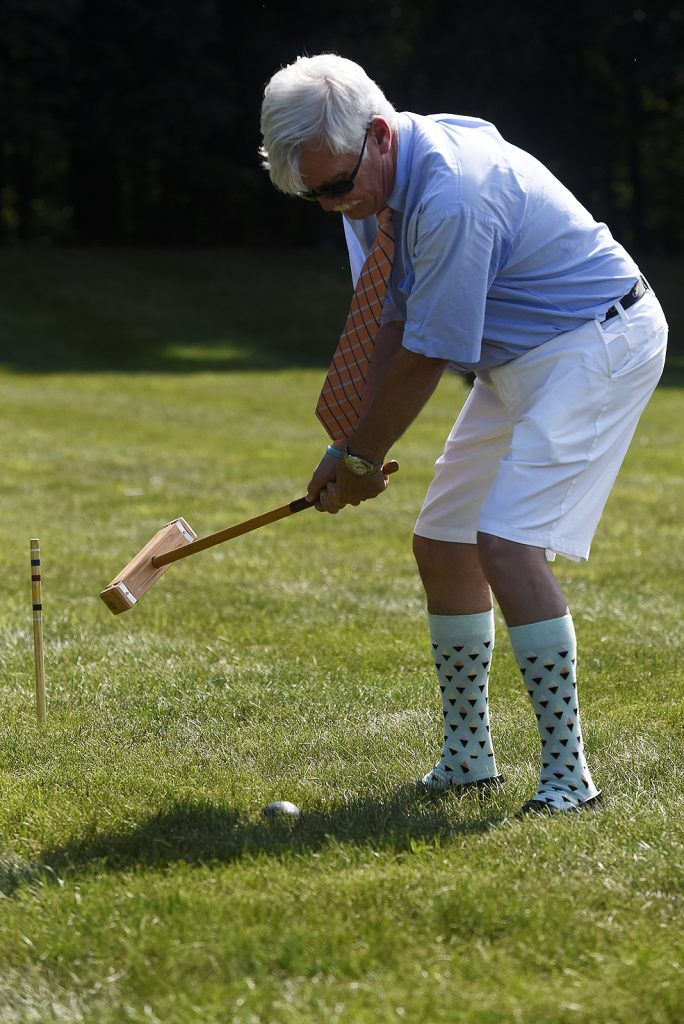 man dressed in goofy high socks rearing back to smack croquet ball
