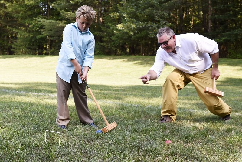 Child learning croquet at Croquet on the Green