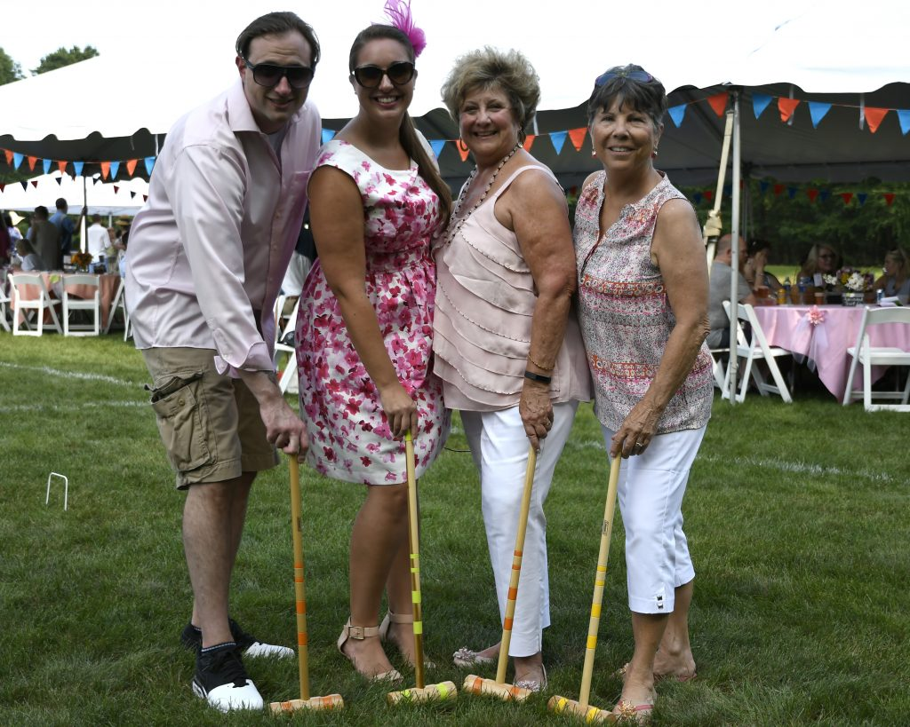 group showing off their yellow and orange mallets at 4th annual croquet on the green