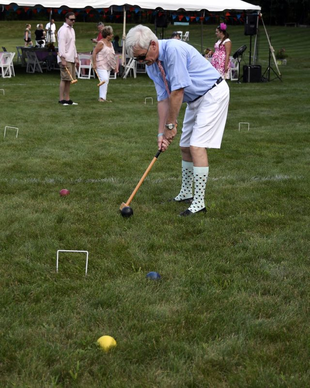 Croquet on the Green man hitting black ball